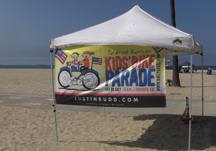 Kids' Bike Parade banner on tent at the beach