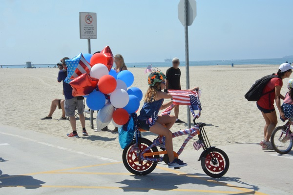 "Great American Kids"" Bike Parade participant with a bunch of mylar balloons tied to her bicycle"
