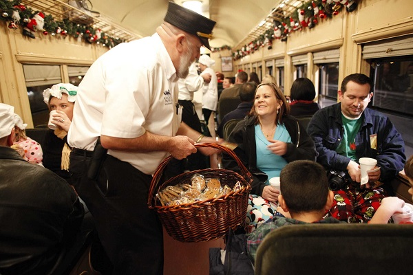 Conductor serves cookies to passengers in Christmas-decorated vintage train car