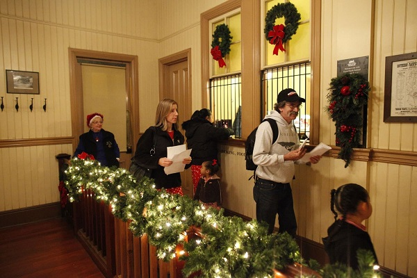 Passengers pick up tickets to THE POLAR EXPRESS™ at the station window.