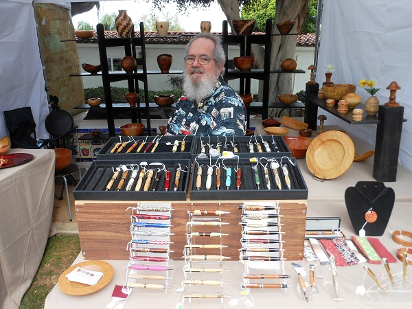 Artist J. Michael Evens in his art booth at a craft fair, surrounded by his hand-turned wooden pens, platters and bowls
