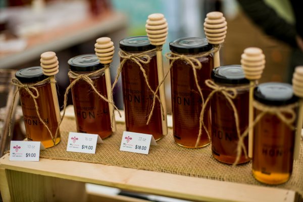 Honey jars with honey rippers on display.