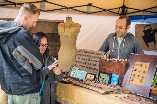 Visitors inspect jewelry made from vintage keys at The Key Historic booth during the Pasdena Jackalope Fair.