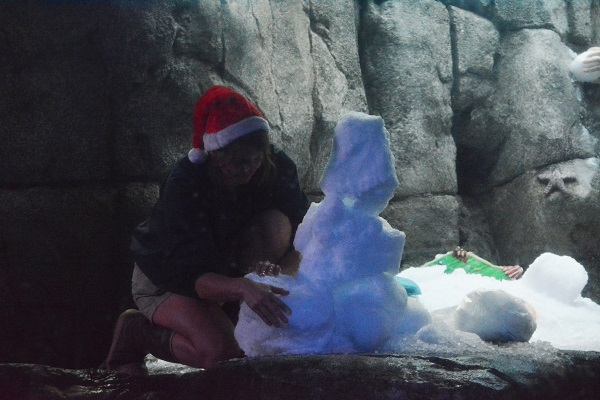 volunteer builds a snowman with treats