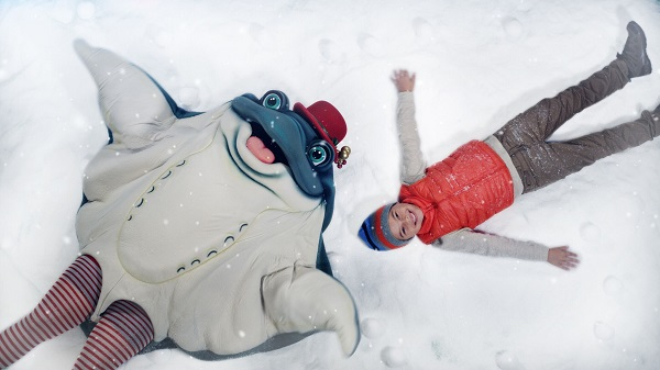 Sea skate character and small boy make snow angels in the snow play area