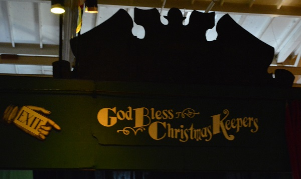 "Green ""God bless the Christmas Keeprs"" sign with gold lettering"