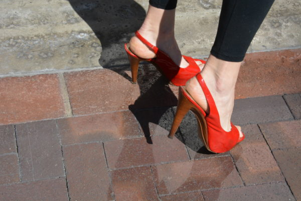2af0ff06258 Closeup of woman s feet as she wears red high heels and jeans and poses on  tile